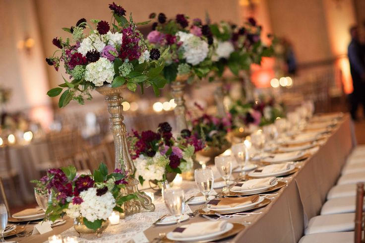 stunning head table for the wedding party is aglow in candlelight and highlighted by a center row of alternating tall gold pedestals and vintage brass low compotes filled with arrangements of purple, burgundy, lavender and white flowers.
