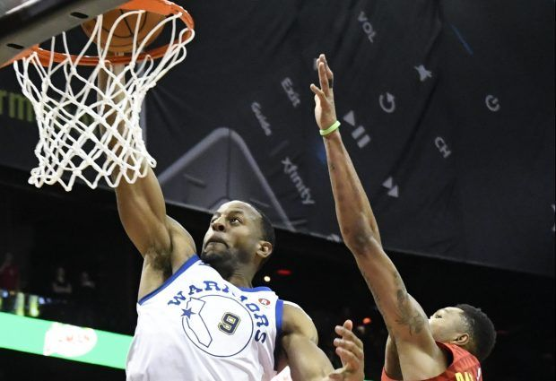 Golden State Warriors forward Andre Iguodala (9) scores against Atlanta Hawks guard Kent Bazemore during the closing moments of an NBA basketball game Friday, March 2, 2018, in Atlanta. (AP Photo/John Amis)
