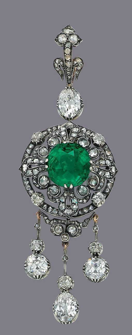 A Colombian emerald and diamond brooch. The circular panel centering a cushion mixed-cut emerald, weighing approximately 14.95 carats, set within a rose and old-cut diamond openwork surround, suspending three rose, old-cut drops, the oval old-cut diamond surmount to the graduated rose-cut diamond pendant loop, with detachable pendant fitting, 10.0 cm, with French import marks for silver and gold