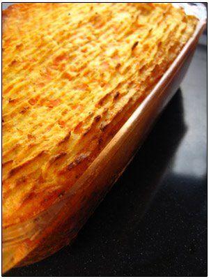 Ovenschotel met gehakt en wortelpuree  500 g bloemige aardappelen 500 g gehakt 1 versnipperde ajuin 1 teentje look, fijn gesneden 1 mager bouillonblokje (runds) 1 koffielepel hot chilisaus 1 potje tomatenpuree 40 g 1 stengel selder in kleine stukjes 1 eetlepel fijngehakte peterselie 300 ml water 2 dikke wortels 2 eetlepel arachideolie 3 eetlepels melk peper, zout en nootmuskaat