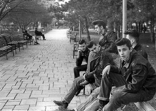 "The ""greaser"" look was very popular among young men in the 50s. Getting their name from the amount of product they used in their hair, they were viewed as the more rebellious crowd, often wearing leather jackets and motorcycle boots with their cuffed denim jeans."