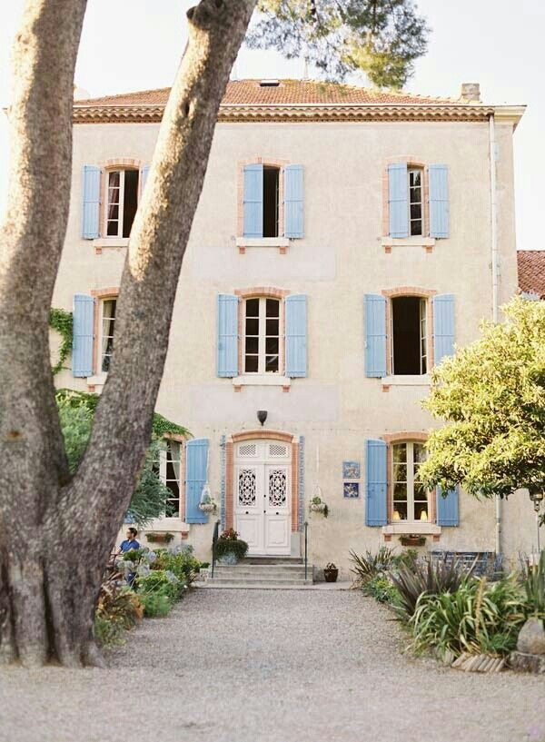 French Country Exterior: Cream with antique blue shutters