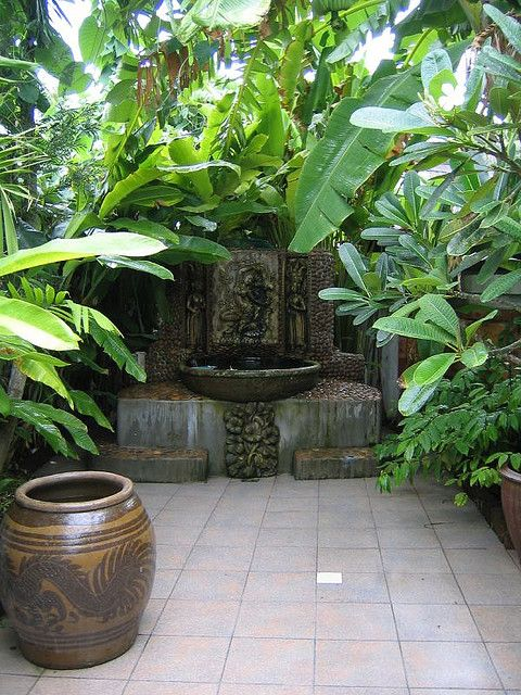 Lush tropical foliage forming a canopy over a fountain.