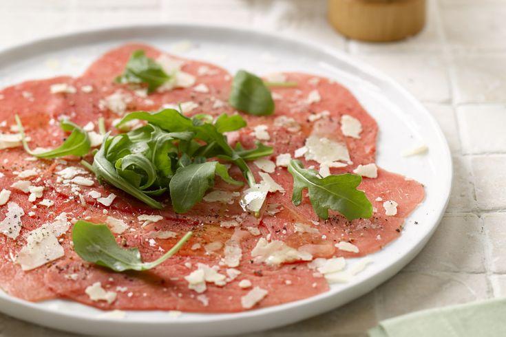 carpaccio - rundvlees, rucola, ... - Verdeel de flinterdunne plakjes rundvlees over 4 borden. Laat ze overlappen. Kruid naar smaak met peper en grof zout.