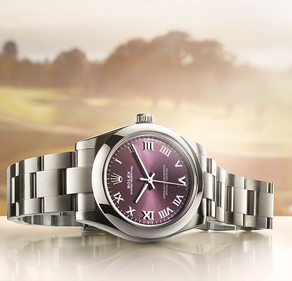 The Rolex Oyster Perpetual 31mm in 904L steel with a red grape dial, against the backdrop of the Evian Resort Golf Club, home of the annual Evian Championship, nestled between Lake Geneva and the French Alps.