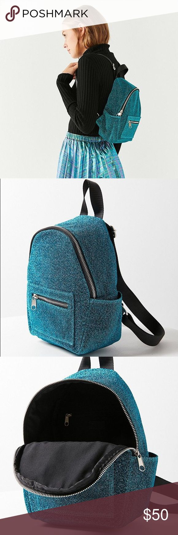 """Turquoise glitter classic mini backpack purse Life's a party so you might as well accessorize accordingly with this glittery mini backpack we're so obsessed with. Kitschy-cute zip-around silhouette with zippered pocket and pouch pockets at sides and front for easy access to your sunglasses + phone. Finished with adjustable shoulder straps and a top carrying handle.  Content + Care - Spot clean   Size - Length: 7.5"""" - Width: 4.5"""" - Height: 10"""" - Handle drop: 4"""" 1.25 Bags"""