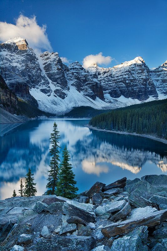 This place is an icon for a reason! First light hits the Valley of the Ten Peaks, reflected in the brilliant blue Moraine Lake. The color of the lake is completely natural (it is due to the high glacial silt content of the water and the physics of light refraction). http://www.janetcampbell.ca/