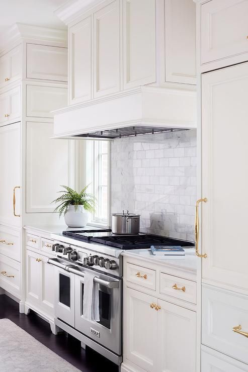 A kitchen hood accented with wainscoting stands over a white marble subway tile backsplash, flanked by windows, placed over a stainless steel stove.