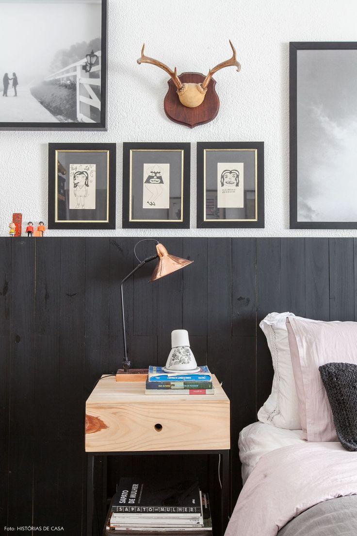 Quarto de casal tem cabeceira de madeira pintada de preto, quadros em tons de…