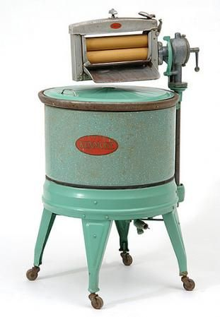 Electric washing machine by Kenmore.  The machine consists of a cylindrical  enamel tub on four castered legs with a drainpipe, motor and wringer and a 1925 patent date on its underside.