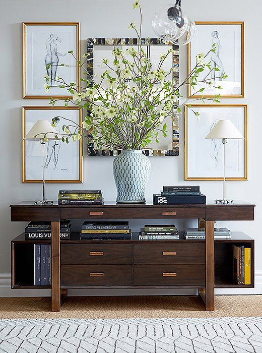 A mediaconsole serves as an artful showcase beneath illustrative figure drawingsthatsoften the cabinet's strong lines.