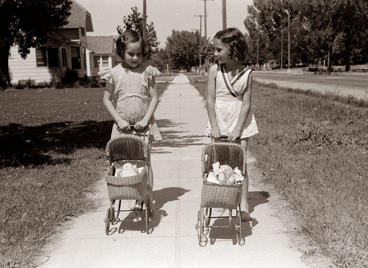 This is a classic picture of bygone days in America. The picture was taken in 1941 in Caldwell Idaho, and shows two little girls taking their dolls for a walk in baby strollers.