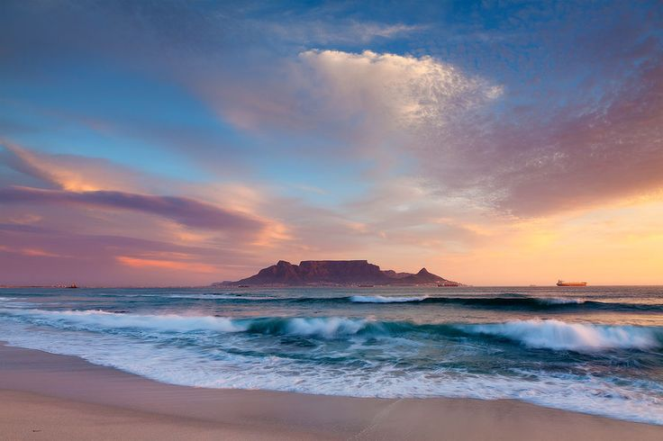 landscape photograph of a typical blouberg beach scene of sunset over table bay looking onto table mountain, cape town, south africa