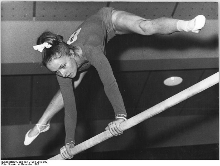 Gymnast Erika Barth performing on uneven bars (1965).