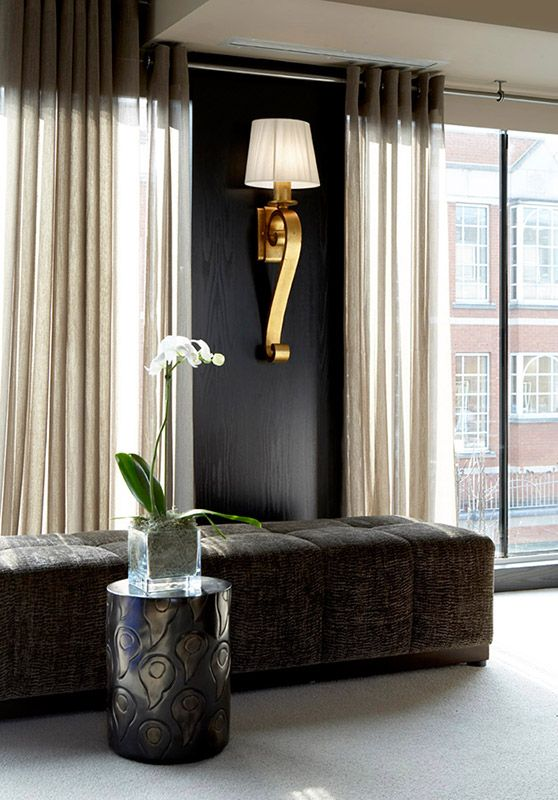 black walls, seating against wall / window. black, gold, grey living room. dark…