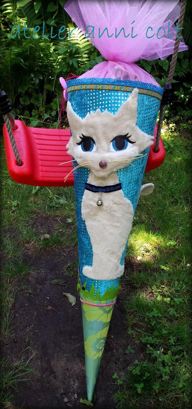Hier biete ich euch eine lustige Katzenschultüte.  Sie ist mit Glitzersamt in Türkis bezogen. Darauf schmunzelt ganz kess eine cremefarbene Katze aus ihren großen blauen Augen. Auf der Rückseite...