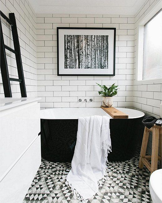 Beautiful black and white bathroom with white subway tiles, black grout, graphic geometric patterned floor, black freestanding bathtub and modern fine art photography.