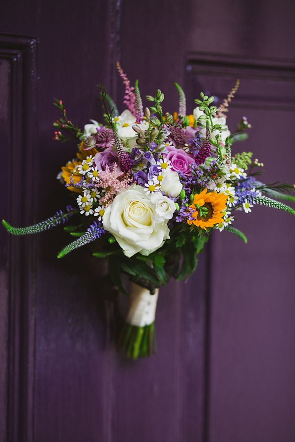 Lovely wedding bouquet featuring a sunflower alongside roses and other wildflower type blooms. http://nickifelthamphotography.com/