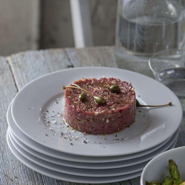 Rindstatar mit Kräuterbaguette. Delikate Vorspeise oder schnelles Hauptgericht: Tatar aus Rindsfilet mit gehackten Kapernäpfeln und Zwiebeln zu Spargelsalat und Kräuterbaguette servieren.