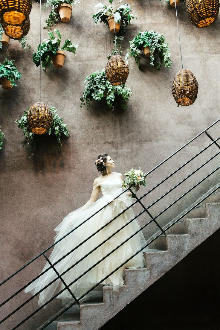 "12 Insanely Inspiring Photos From NYC's Most Gorgeous Weddings #refinery29  http://www.refinery29.com/gorgeous-nyc-wedding-pictures#slide-10  Jennifer & Caleb, Meatpacking District""The bride wore this stunning, flowy wedding dress made by Carol Hannah. It reminded me of a beautiful waterfall. I wanted to put her on the steps with the backdrop of the hanging plants and lanterns to create this image — like a waterfall cascading down to the creek."" - Matthew Lee"