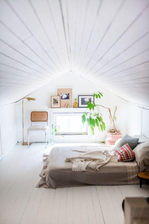 Attic bedroom with white painted wood walls and floors