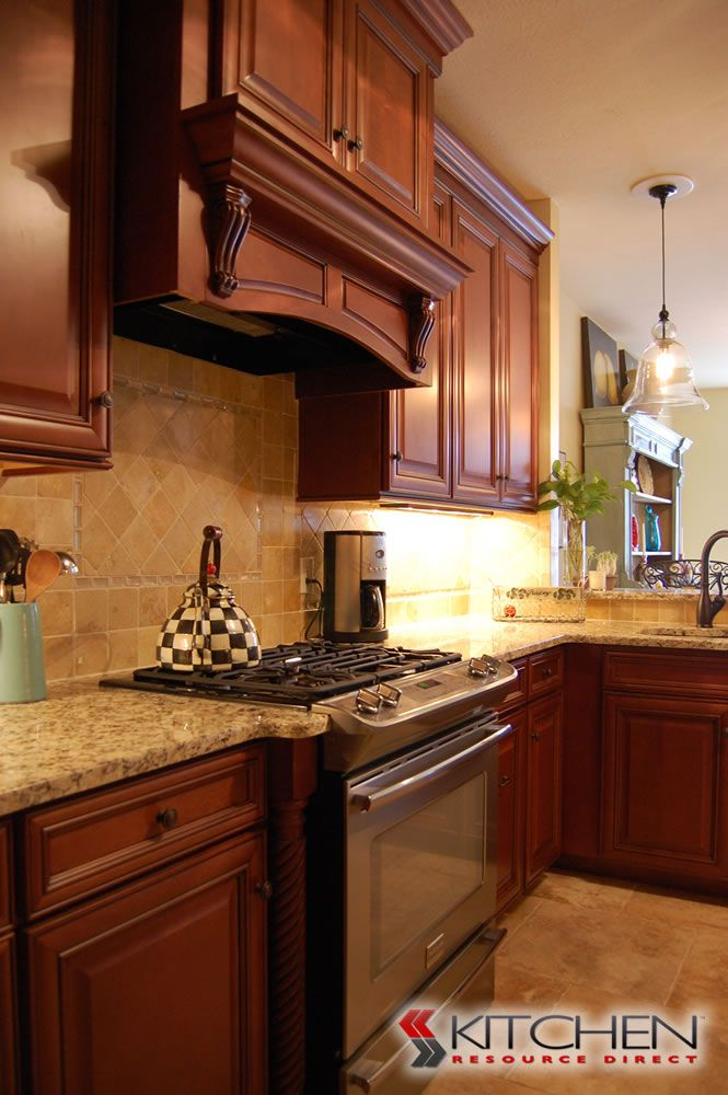 Beautiful traditional kitchen with medium stained cabinet finish; stainless steel appliances; wooden range hood