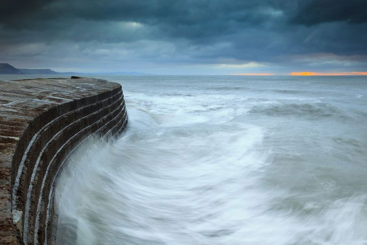 A large wave swirling at The Cobb in Lyme Regis in Dorset on a Winter morning. Andy Ferrar