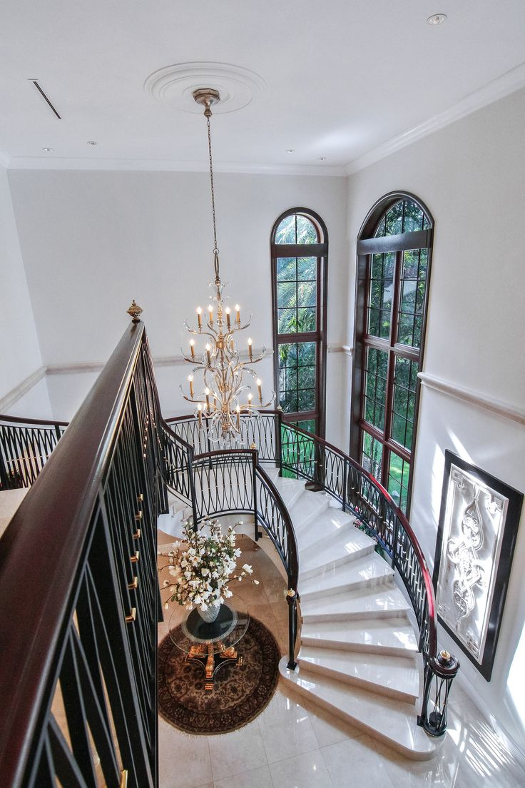 As you step into the foyer at Villa Dwora, an oversized marble staircase with custom iron railing that wraps around an elegant crystal chandelier and coffered ceilings are just a few details that invite you in! #SupremeAuction #LuxuryAuction #Miami #CoralGables #MiamiMansion #MiamiRealEstate #Florida #FloridaRealEstate #ResortStyle #Auction #KoiPond #MediterraneanMansion