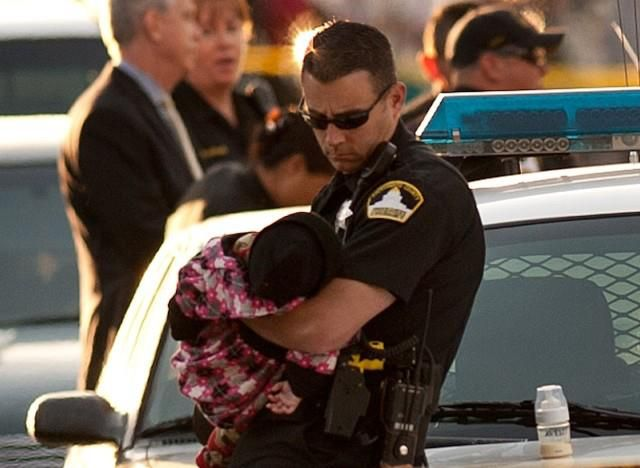 Cop holds baby whose mother and siblings were killed. - Imgur
