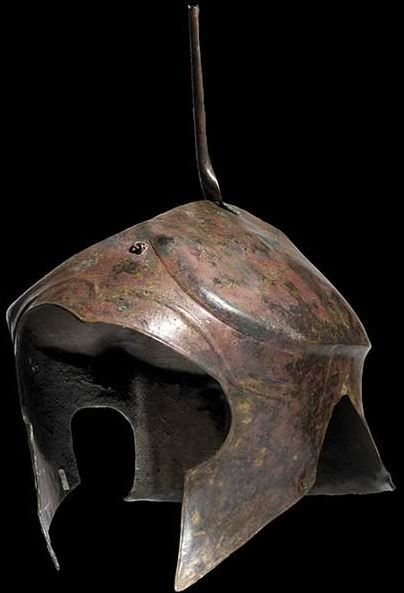 Chalcidian helmet, 5th - 4th century B.C. Helmet with clearly offset, elongated calotte, steep crown ridge and a pronounced forehead field beneath the gabled brow with a large face cutout. Soldered to the crown a tall, rolled bronze sheet metal, crest holder. On the forehead and the neck guard an eyebolt with a ring for attaching the helmet crest, pointed cheek pieces, 25 cm high, without top piece Private collection, from Hermann Historica auction