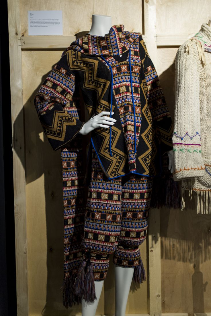 """Suit by Bill Gibb, 1976, Acrylic From the KNITWEAR Chanel to Westwood exhibition Image (c) Fashion and Textile Museum This knitted tunic pullover, pantaloons and scarf set are from the """"Byzantine"""" collection by Bill Gibb and his partner Kaffe Fassett. Fassett would hand dye and knit sample swatches which would then be made by technician Mildred Boulton, into garments designed by Gibb. This set uses 7 colours on the two designs but Boulton had knitted up to 20 colours in one garment."""