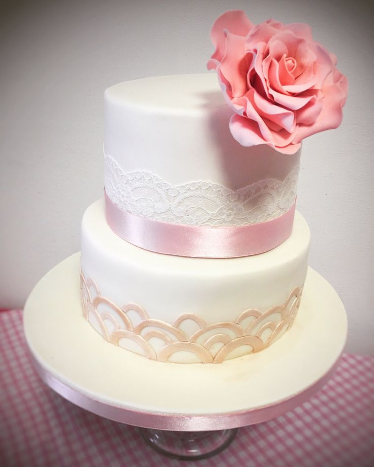 Wedding Cake - 2 tier cake in White Fondant with gold Art Deco Details, Lace, and a large Pink Sugar Rose