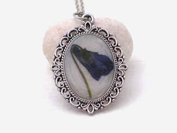 This pendant is made with a pressed violet (by me from Hungary). The violet is laid on nacreous resin on a platinum plated oval bezel.