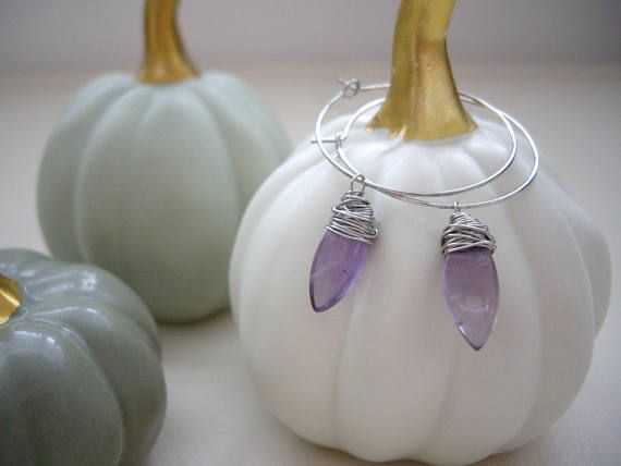 Beautiful purple transparent amethyst is generously wrapped and dangles from 3 cm hoop earrings. Messy wrap is on trend right now and these delicious earrings have it going on! Wear them with your favorite jeans, your business casual or your Sunday best. These beauties can do it all.  *READY TO SHIP. FREE GIFT WRAP. If youd like to have in gift wrapped, Please leave a note to seller.  Materials used: Amethyst Artistic Wire Base metal hoop earrings Measurements: Size of amethyst : 0.6 x 0.3…