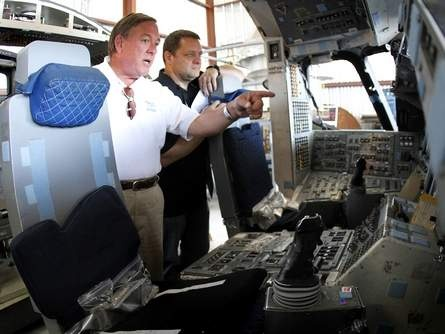 Capt. Bob Oehl, the co-founder of the Wings of Dreams Aviation Museum at the Keystone Heights Airport, points out some to the features of the Space Shuttle Simulator, which was delivered to the museum Tuesday, April 24. Mike Potapow, a founding member of the museum, is at right. (Brad McClenny/Staff photographer)