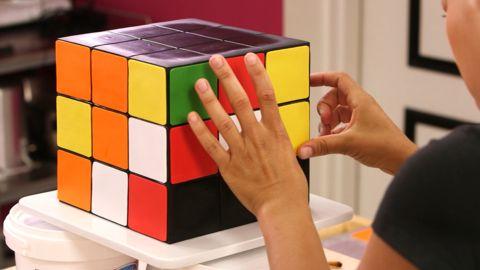 I don't know how to solve a Rubik's Cube, but I know how to slice one! I made a Vanilla Rubik's Cube Cake with Black Chocolate Ganache & Yellow Buttercream.