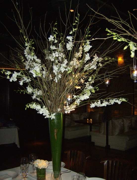 A tall leaf wrap with branches and bright orchids to