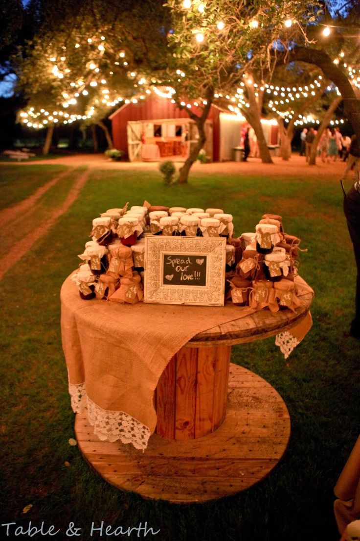 Homemade jam favors at rustic wedding reception, displayed on wooden spool - Table & Hearth