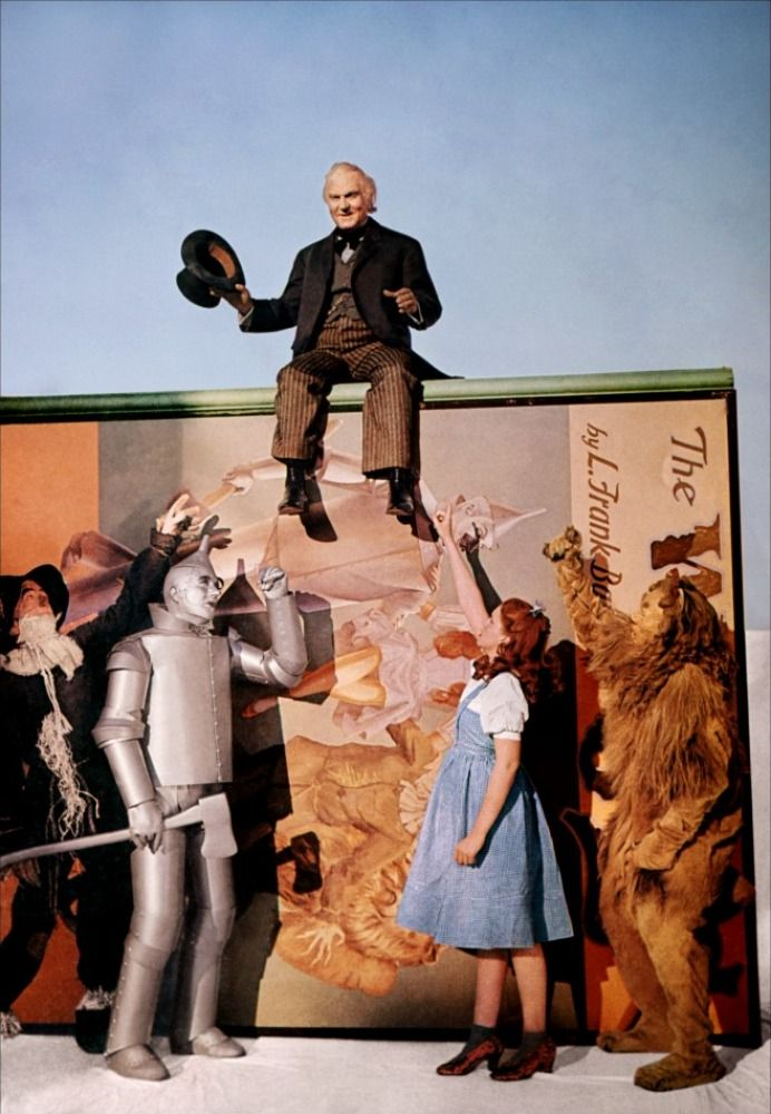 "2/20/14 10p  MGM ""The Wizard of Oz""   Professor Marvel/The Wizard  sits atop a large Prop Poster Book of the Film.  Standing: Scarecrow  Tin Man Dorothy Gale  Cowardly Lion  1939"