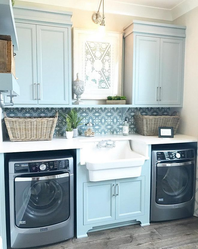 Laundry room features blue gray cabinets and a farmhouse sink flanked by a pair of gray washer and dryer. Countertop is white quartz and backsplash is a patterned cement tile.