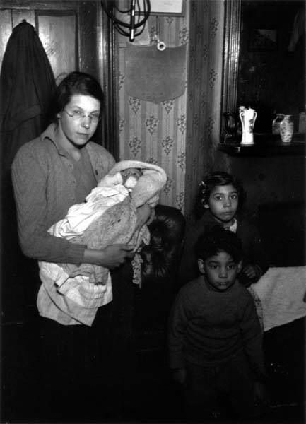 Mrs. Mix and her three children in their flat at Hanbury Buildings, Poplar, East London. 1939