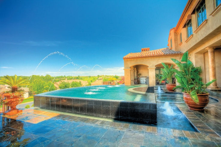 The elegance of the home demanded that the pool be equally sophisticated. Mission accomplished: the perimeter-overflow (which functions like a 360-degree vanishing edge) spills gently over a tiled wall into a pool that includes fountains and a submerged spa. Deck jets add an unexpected touch of merriment. Advanced Pool Designs, Rancho Cordova, California. Photo courtesy of Brad Taylor Photography