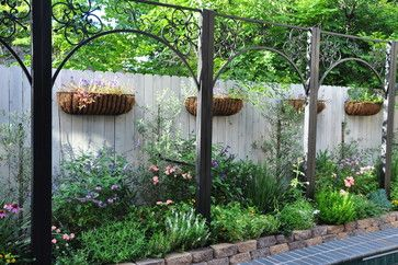 Soften fence with hanging baskets and arbor -Braeswood Place Pool and Courtyard traditional landscape