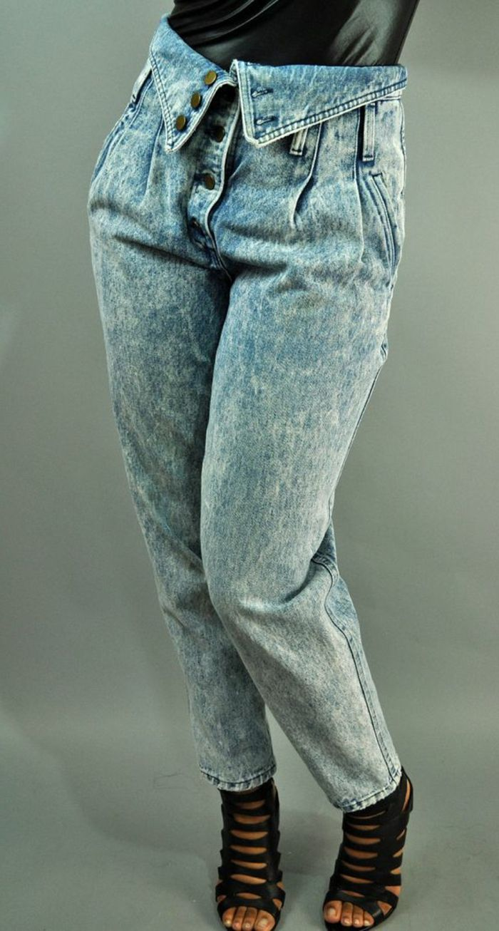 b0893280f3c3c close up of woman s lower half, wearing high-wasted acid wash jeans with  button fold over detail, black sandals with many straps and black shiny top