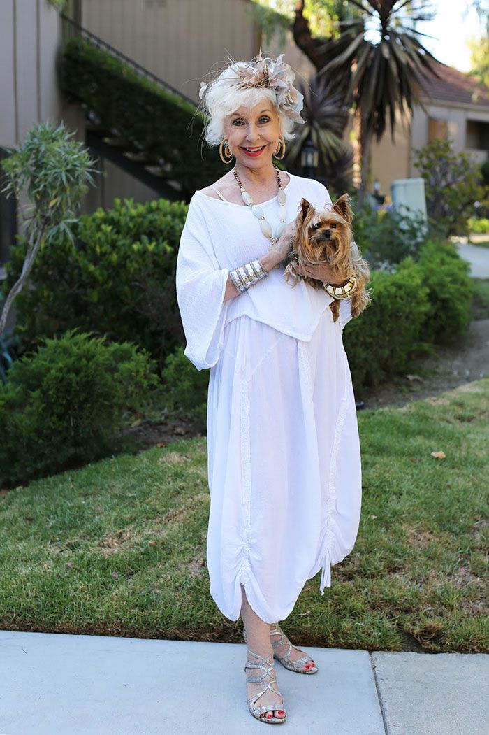 Mujer mayor usando un traje en color blanco y sosteniendo un perro