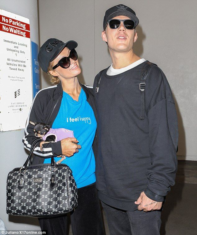 Beaming beauty! Paris Hilton was all smiles while gazing at new beau Chris Zylka at the LAX airport on Tuesday