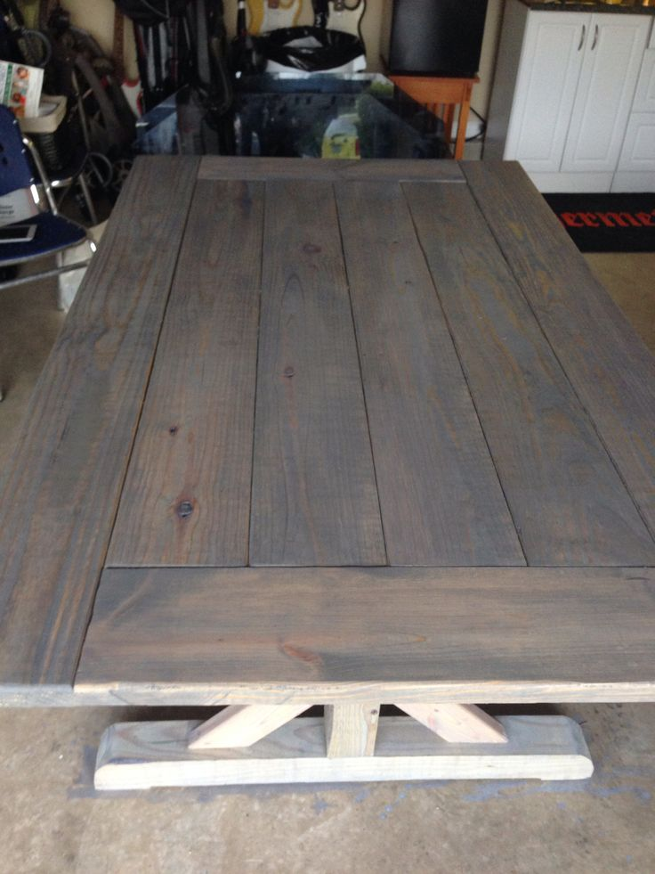Handmade farm house table with reclaimed wood First coat of grey color stain