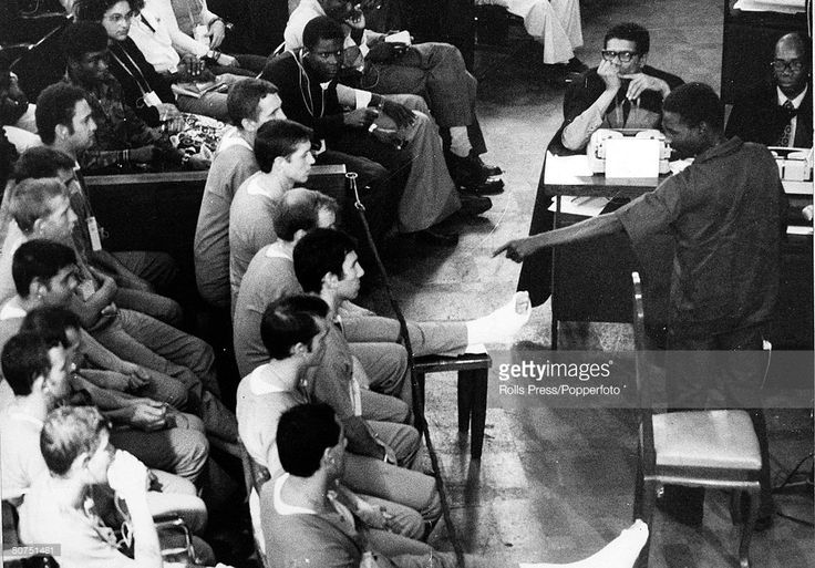 June 1976, Luanda,The accused men in the dock, including Costas Georgiou (Colonel Tony Callan) at the show trial where 13 mercanaries, 10 of them British were being tried, A man points an accusing finger at one of the accused men