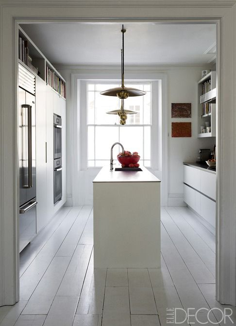Israel-born restaurateur and cookbook author Yotam Ottolenghi commissioned British firm Roundhouse to create a minimalist kitchen for his North London home. Sunlight floods the room, which features a central island with a sink and shelving for favorite cookbooks. - ELLEDecor.com