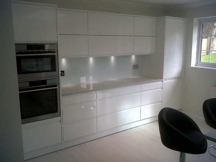 A white back painted toughened glass kitchen splashback.